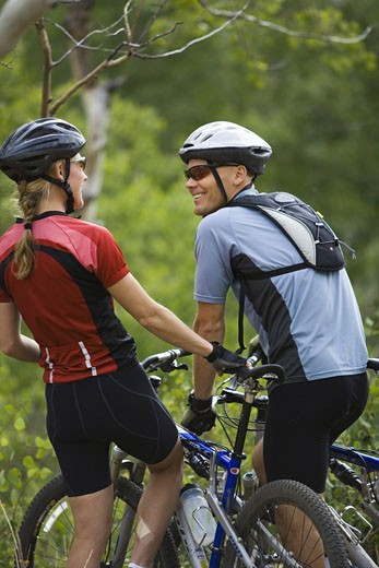 Stock Photo: 1660R-3452 Rear view of a couple mountain biking