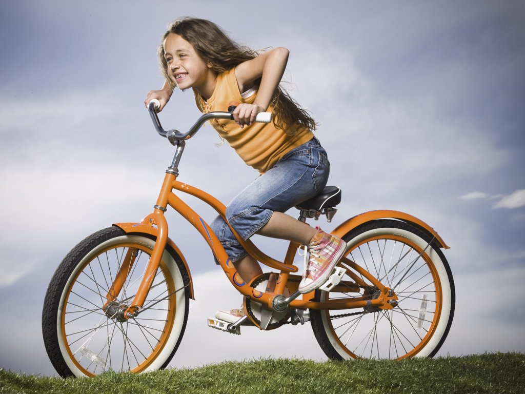 Stock Photo: 1660R-34537 Girl sitting on orange bicycle outdoors smiling