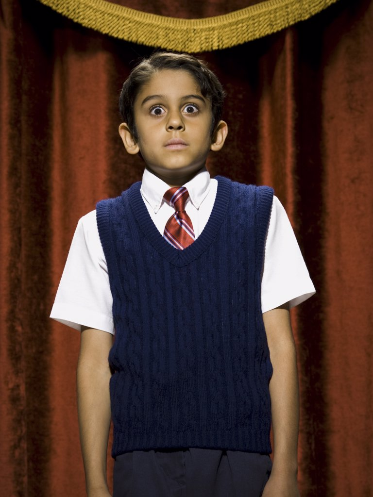 Stock Photo: 1660R-34550 Boy standing on stage with microphone and big eyes