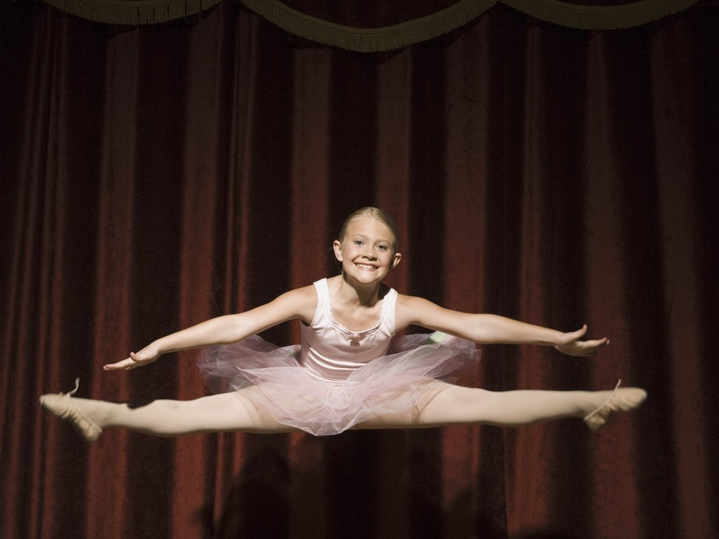 Ballerina girl on stage leaping and smiling : Stock Photo