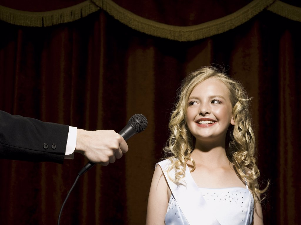 Stock Photo: 1660R-34670 Girl beauty pageant contestant with microphone looking nervous
