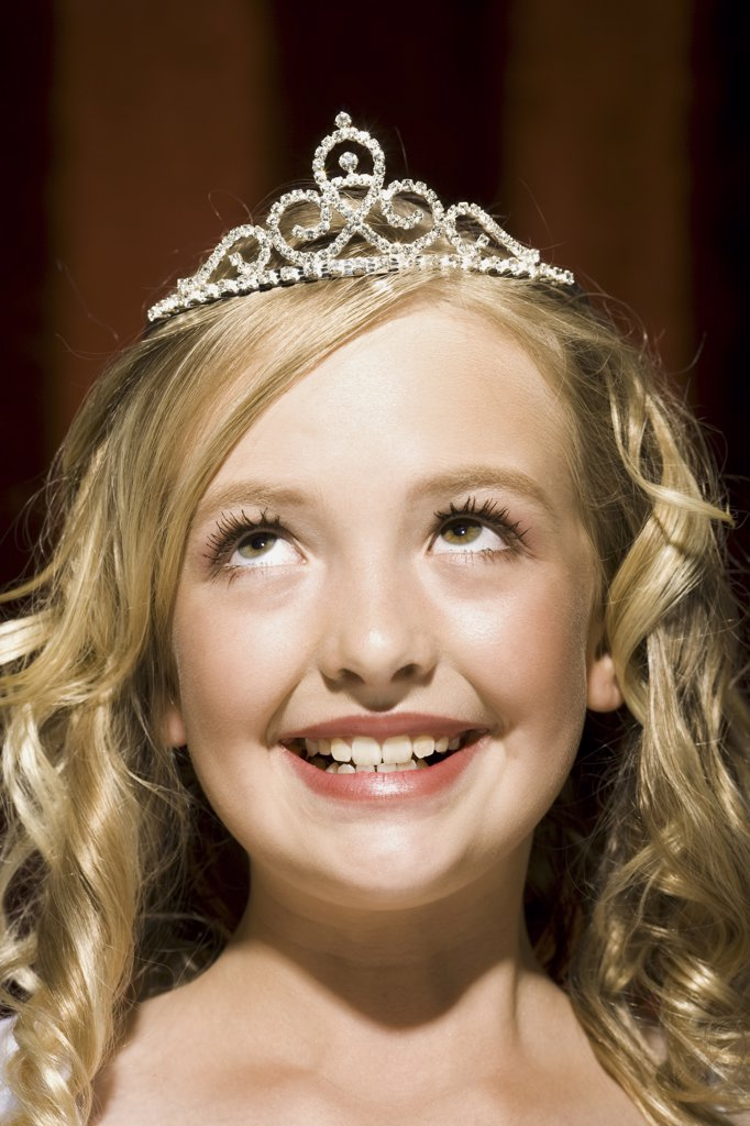 Closeup of girl with tiara looking up smiling : Stock Photo