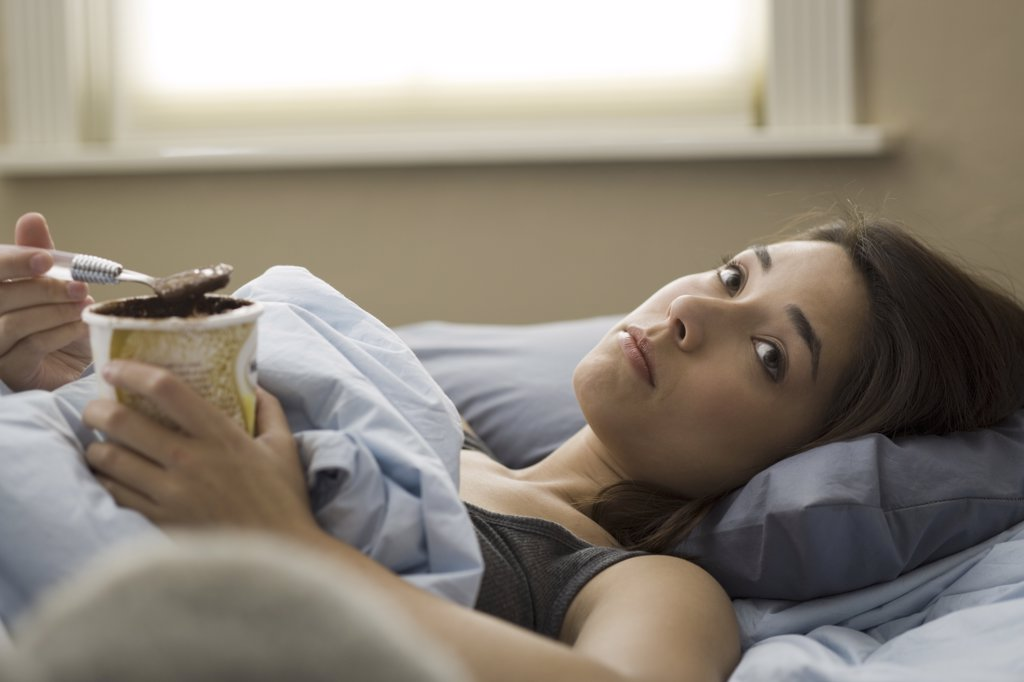 Woman lying in bed eating chocolate ice cream : Stock Photo