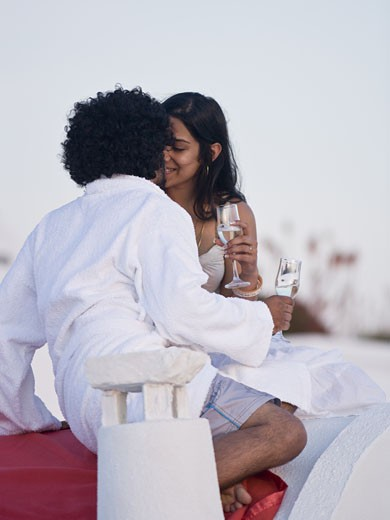 Stock Photo: 1660R-35114 Couple kissing and snuggling outdoors with champagne flutes