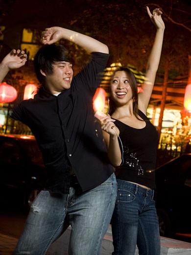 Stock Photo: 1660R-35177 Couple listening to mp3 player outdoors dancing and smiling