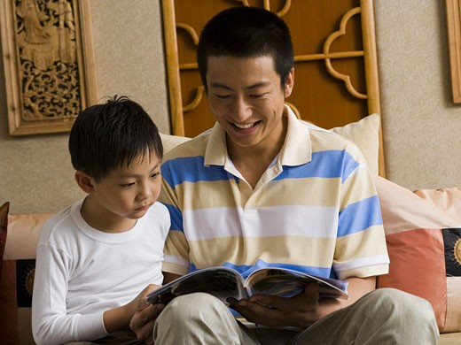 Stock Photo: 1660R-35204 Father and son reading magazine
