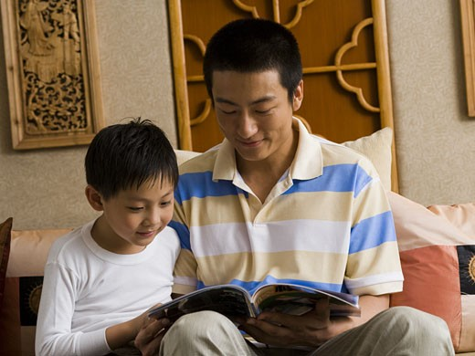 Father and son reading magazine : Stock Photo
