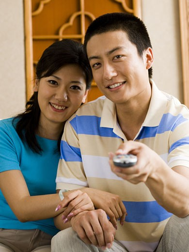 Couple sitting on sofa watching television smiling : Stock Photo