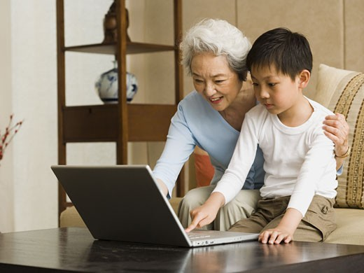 Grandmother and grandson with laptop : Stock Photo