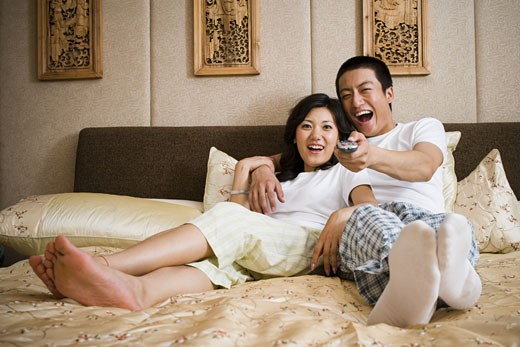 Stock Photo: 1660R-35248 Couple in bed snuggling and watching television