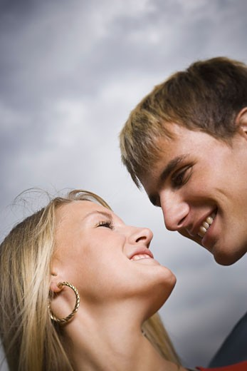 Close-up of a teenage couple looking at each other : Stock Photo