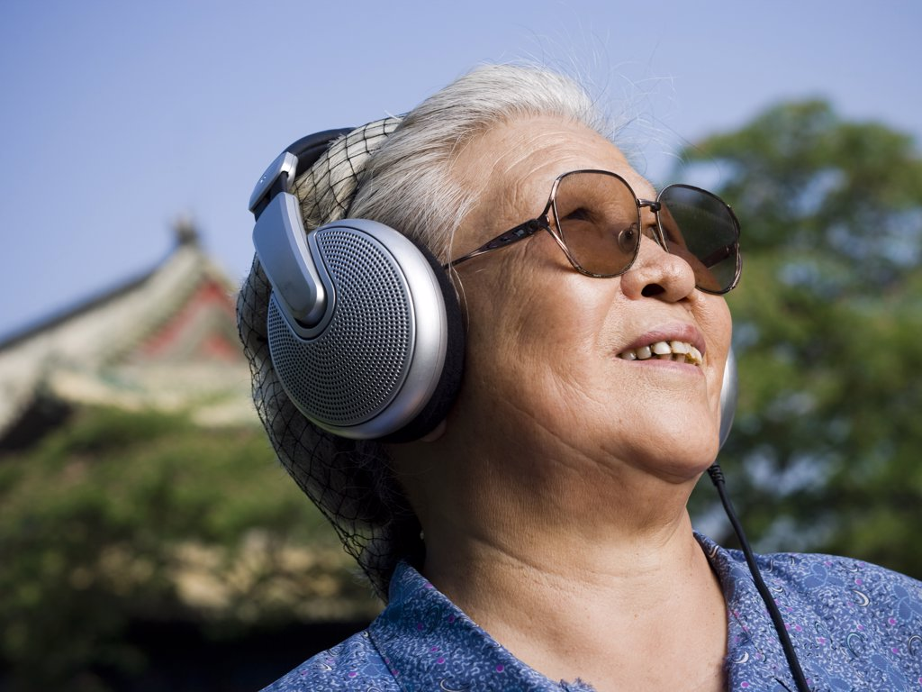 Mature woman outdoors with headphones smiling : Stock Photo