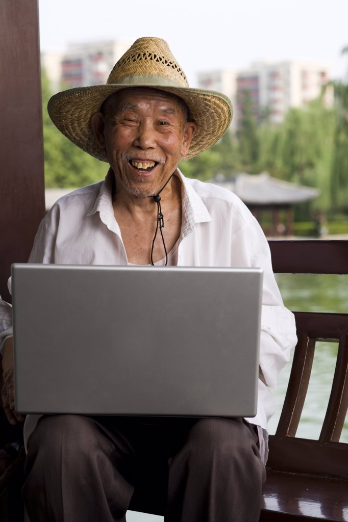 Stock Photo: 1660R-35798 Mature man with straw hat and laptop outdoors