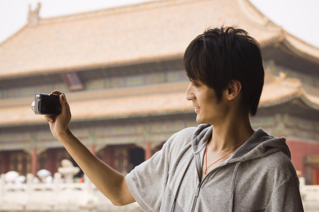 Stock Photo: 1660R-35861 Teenage boy outdoors with digital camera smiling