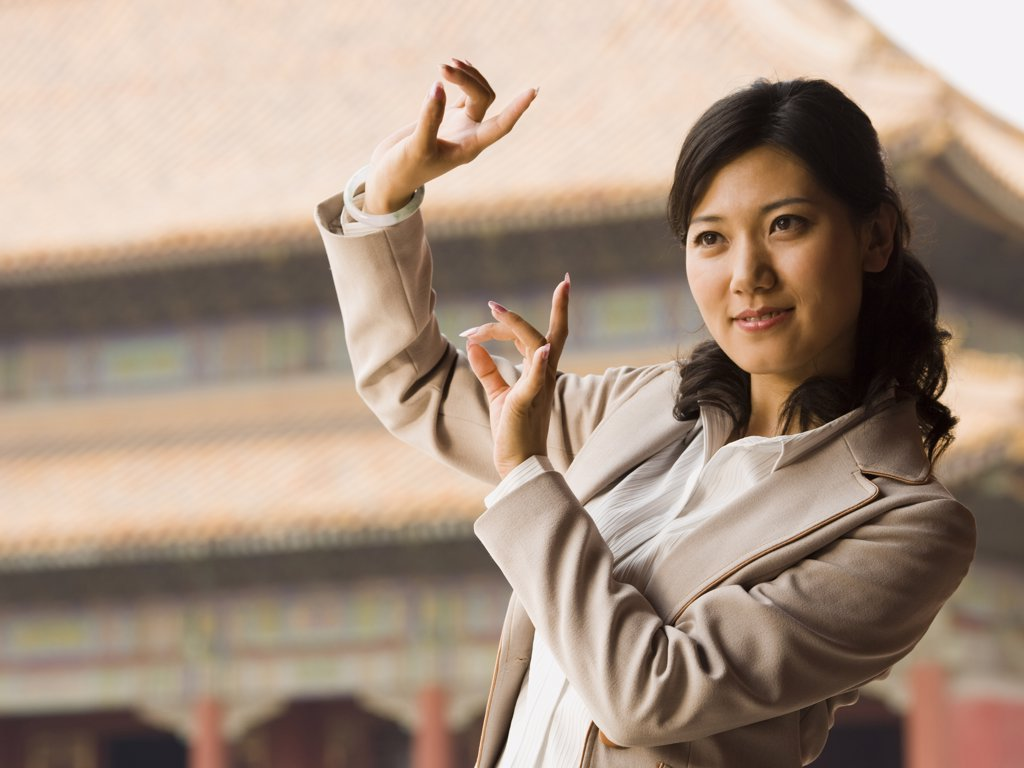 Businesswoman doing tai chi outdoors smiling : Stock Photo