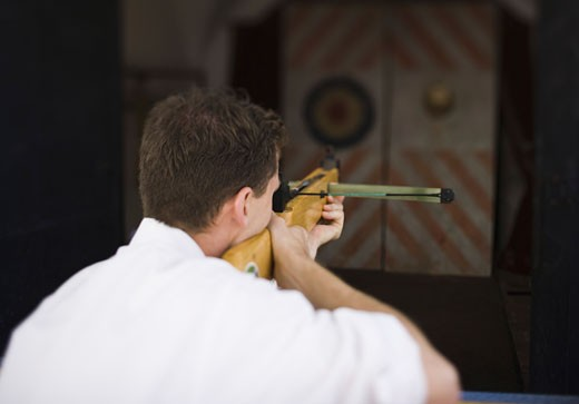 Stock Photo: 1660R-3626 Rear view of a young man target shooting