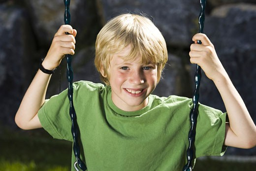 Portrait of a boy sitting on a swing : Stock Photo