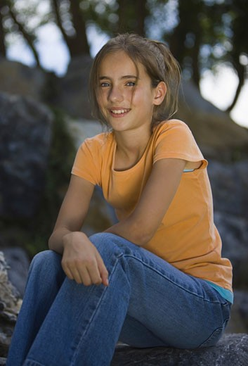 Stock Photo: 1660R-3697 Portrait of a girl sitting on a rock