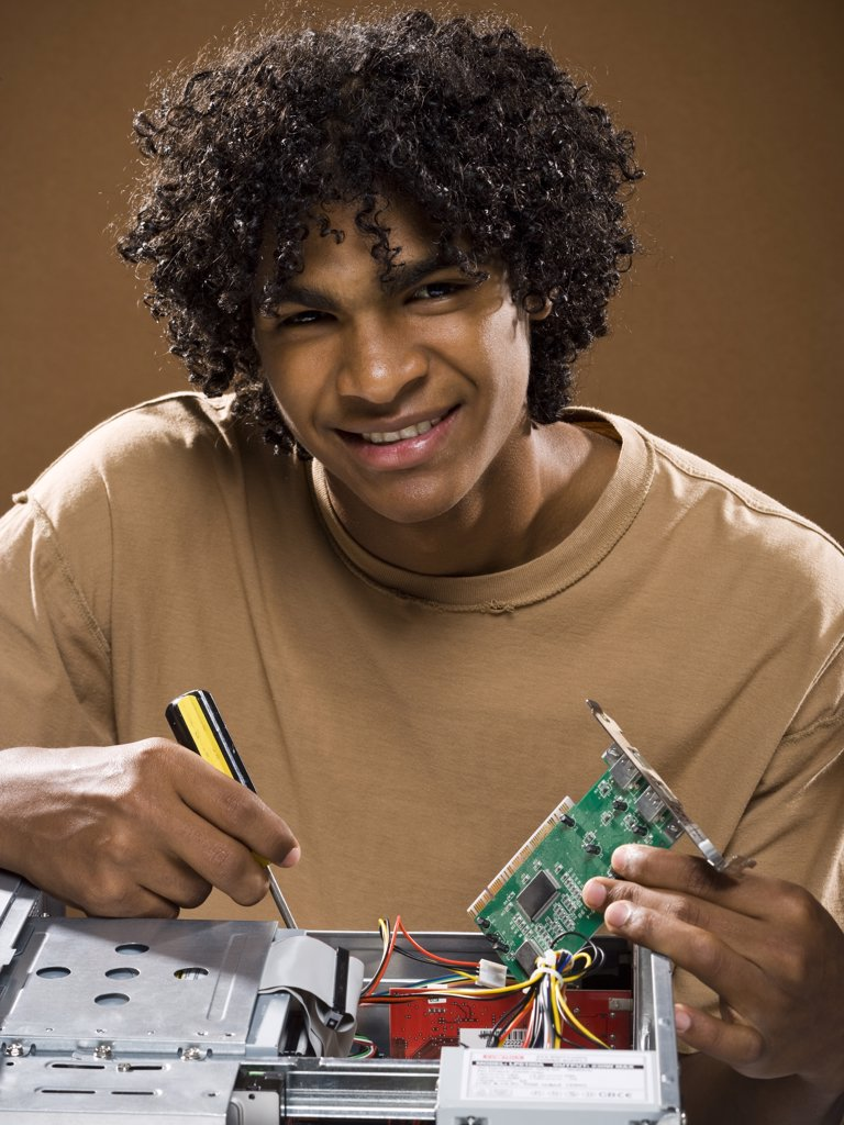 Stock Photo: 1660R-36985 young man in a brown shirt fixing a computer.