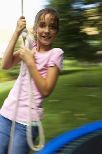Stock Photo: 1660R-3702 Portrait of a girl swinging from a rope