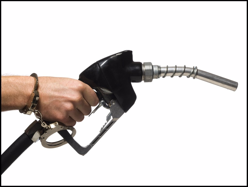 Hand handcuffed to a gas pump. : Stock Photo