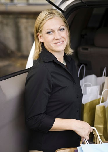 Stock Photo: 1660R-3750 Portrait of a young woman holding shopping bags