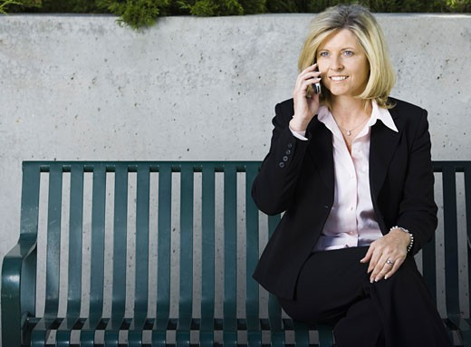 Stock Photo: 1660R-3774 Businesswoman sitting on a bench and talking on a mobile phone