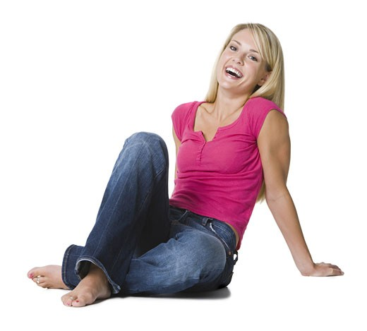 Portrait of a young woman sitting on the floor : Stock Photo