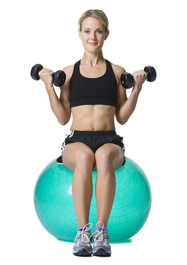 Stock Photo: 1660R-3830 Portrait of a young woman sitting on a fitness ball holding dumbbells
