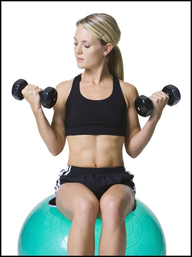 Stock Photo: 1660R-3831 Young woman exercising with dumbbells