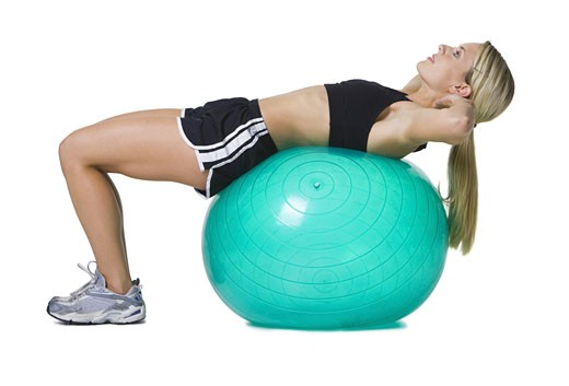 Profile of a young woman lying on a fitness ball : Stock Photo