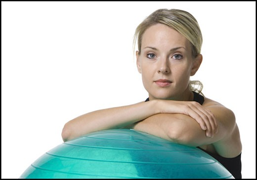 Portrait of a young woman leaning on a fitness ball : Stock Photo