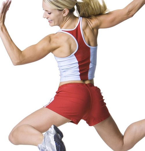 Rear view of a young woman jumping : Stock Photo