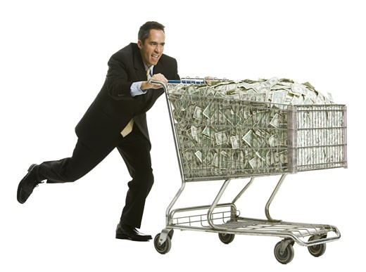 businessperson with a shopping cart full of money : Stock Photo