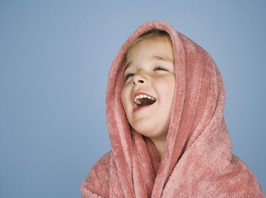 Close-up of a girl laughing with a blanket wrapped around her head : Stock Photo