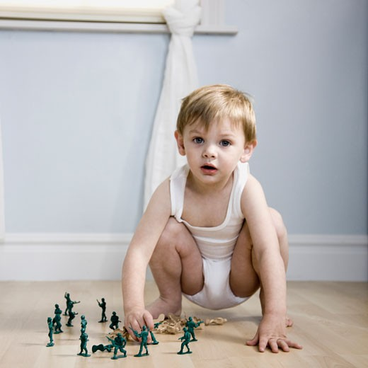 Stock Photo: 1660R-40053 little boy playing with toy soldiers