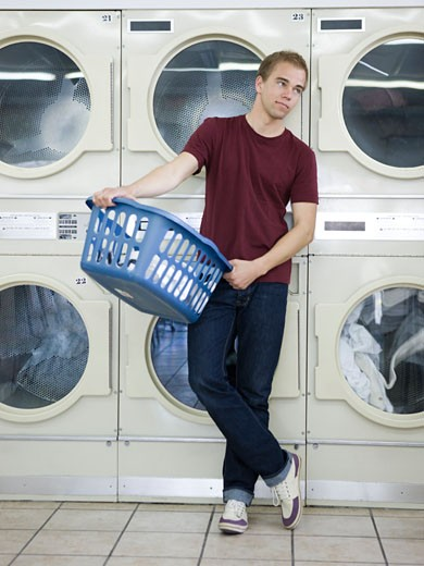 Stock Photo: 1660R-40266 man doing laundry at a laundromat