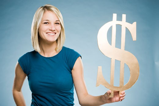 woman holding up a dollar symbol : Stock Photo