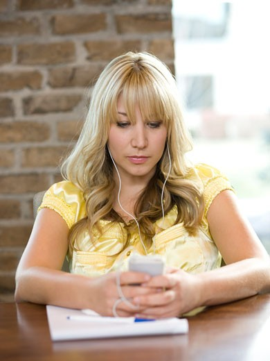 Stock Photo: 1660R-41653 woman using her cell phone during a meeting