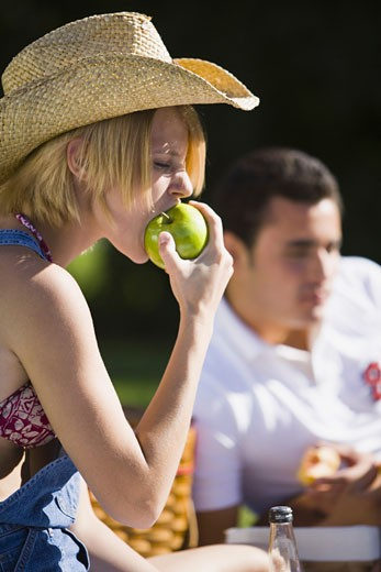 Close-up of a young woman biting an apple : Stock Photo