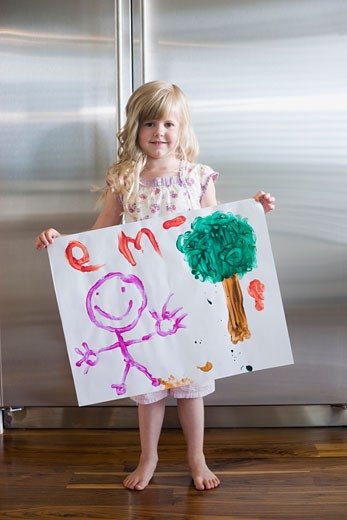 little girl holding up a drawing : Stock Photo