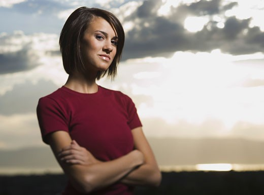 Stock Photo: 1660R-4213 Portrait of a young woman standing with her arms crossed