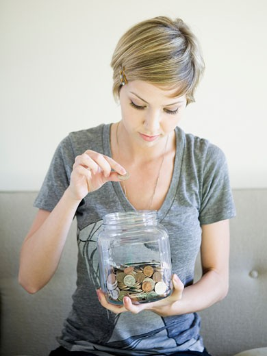 Stock Photo: 1660R-42291 woman sitting on couch with a jar of coins