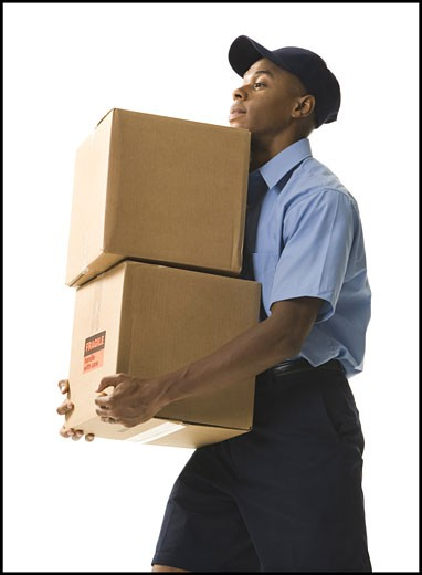 Profile of a young man carrying cardboard boxes : Stock Photo