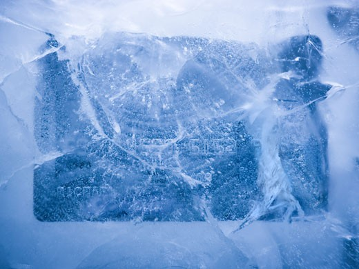Stock Photo: 1660R-44221 credit card frozen in a solid block of ice