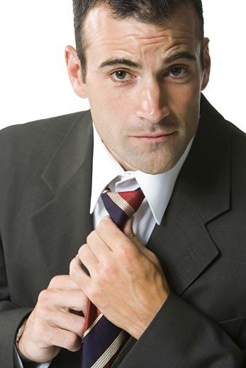 Portrait of a businessman adjusting his tie : Stock Photo