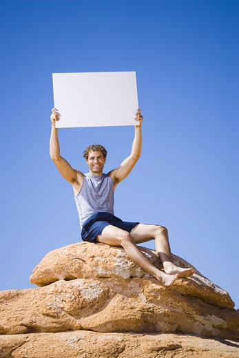 Low angle view of a young man sitting on a rock with a blank sign holding up : Stock Photo