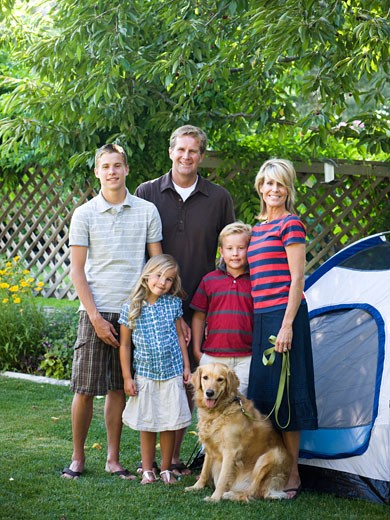 family standing in their backyard with a tent and their dog : Stock Photo