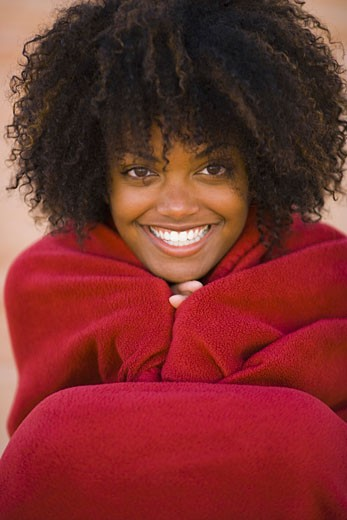 Portrait of a young woman wrapped in a blanket, smiling : Stock Photo