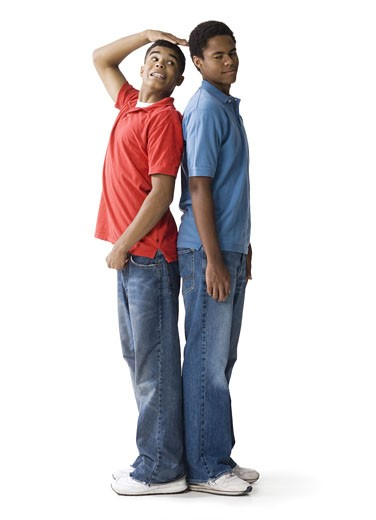 Stock Photo: 1660R-4576 Profile of a teenage boy and a young man standing back to back